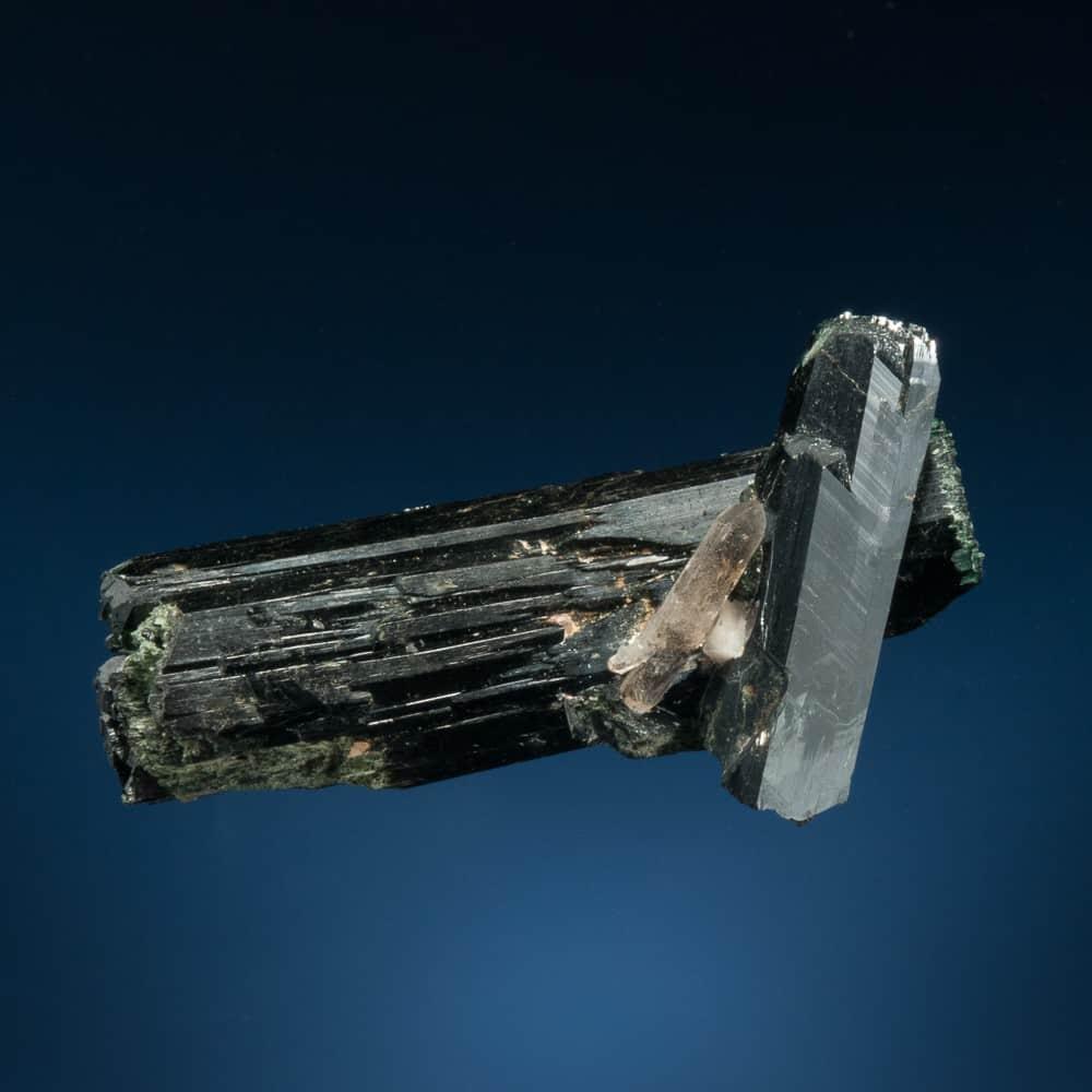 Dos cristales de aegirina afilados, lustrosos e intercalados con un cristal de cuarzo