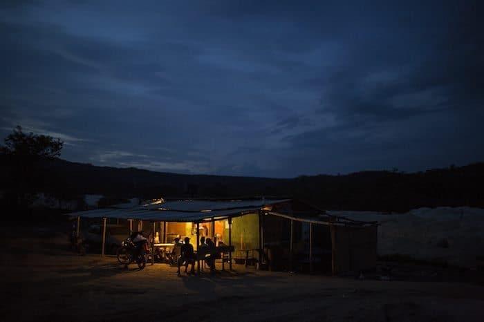Mineros artesanales de diamantes en un bar iluminado al anochecer. En raras ocasiones, los mineros encuentran diamantes y consiguen decenas de miles de dólares. Foto: AP