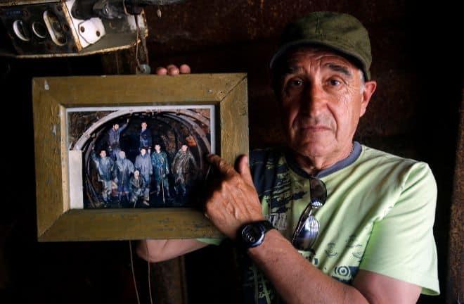Manuel Moure, junto a la foto de los mineros fallecidos, uno de ellos su hijo.